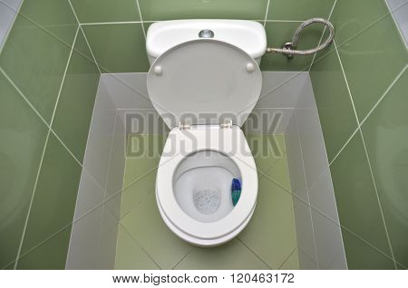 Open Water Closet With Green Tiles In Background