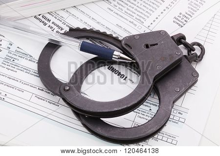 Handcuffs With Pen On Tax Form Background