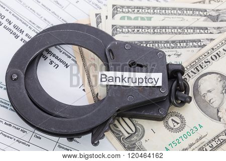 Handcuffs And Money With Sign – Bankruptcy On Tax Form Background