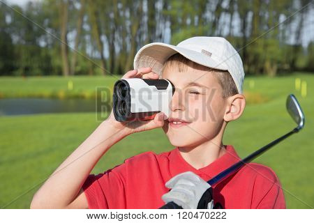 boy golfer watching into rangefinder