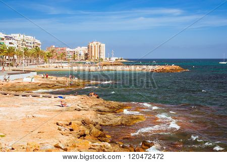 Sunny Mediterranean Beach, Tourists Relax On Warm Shore Of Sea On Loungers Under Parasols, Paseo Jua