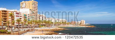 TORREVIEJA, SPAIN - SEPTEMBER 13, 2014: Sunny Mediterranean beach Tourists relax on warm shore of sea on loungers under parasols. People bathe in crystal clear salty water of sea Paseo Juan Aparicio, Torrevieja, Valencia, Spain