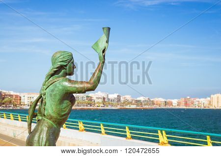 Bronze Monument Of Woman With Letter In Hand, Which Accompanies Sailor. Pedestrian Bridge-pier, Mari