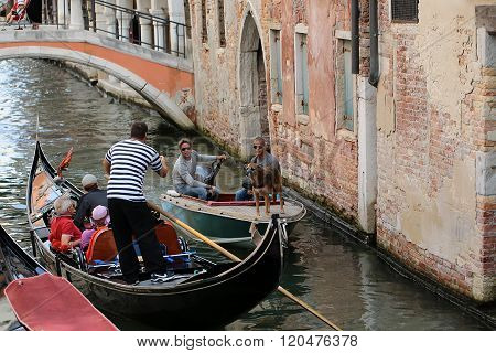 VENICE ITALY - SEPTEMBER 22, 2015: Wooden black typical gondola with tourists and sculling gondolier speaking with two men and dog in boat on Grand canal near old brick building outdoor horizontal picture