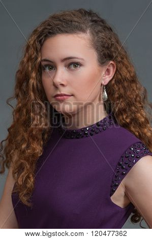 Teen beauty in purple dress showing serious expression to left.