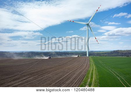 Windmill and The Tractors Harrowing The Field