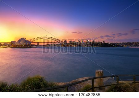 Australia Sydney city CBD view from Mrs Macquarie's Chair over harbour waters at sunset highly illuminated buildings and houses reflecting lights in blurred water