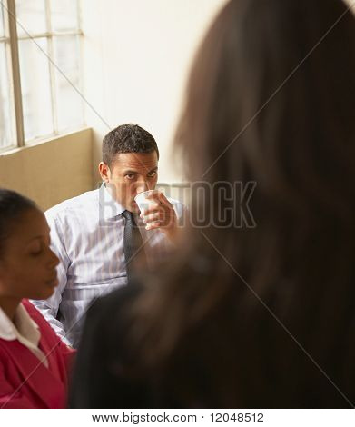 Businessman drinking coffee in a meeting