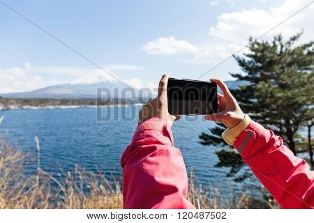 Woman take the photo by cellphone for Mountain Fuji