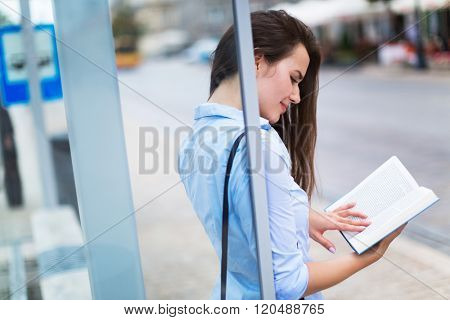 Woman reading book while waiting for bus