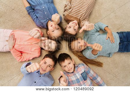 childhood, fashion, gesture and people concept - happy smiling children showing thumbs up and lying on floor in circle