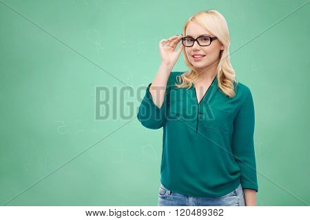 vision, optics, education and people concept - smiling young woman with eyeglasses over green school chalk board background