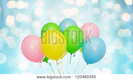 holidays, birthday, party and decoration concept - bunch of inflated colorful helium balloons over blue lights background