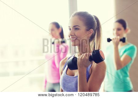 fitness, sport, training and lifestyle concept - group of happy women with dumbbells flexing muscles in gym