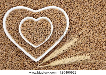 Spelt grain health food in heart shaped bowls with wheat sheaths forming an abstract background.