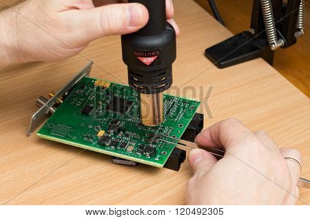 Man's Hand Holds The Soldering Station