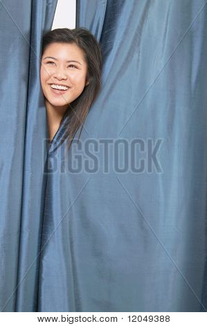 Woman smiling and peeking out from dressing room
