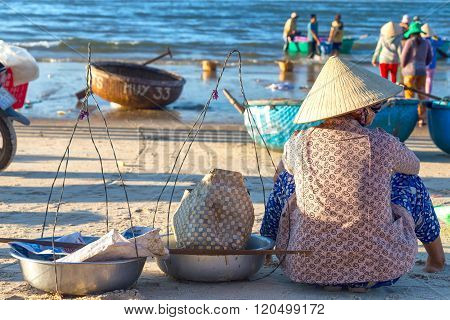 Woman waiting for fish to buy coastal fishing village