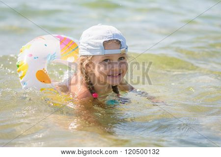 Happy Four-year Girl Floats With A Circle In The Sea Water