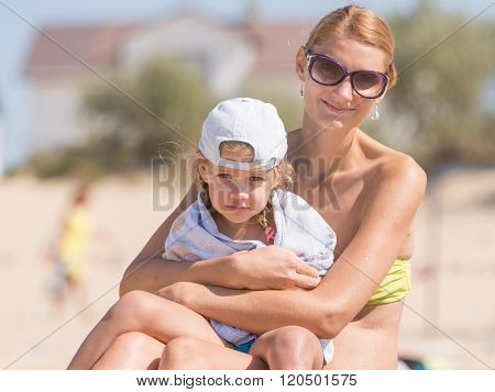 Young Mother Warms Her Frozen Daughter On The Sandy Banks Of The River