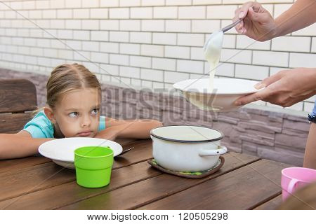 Upset Six-year Girl Dissatisfied Looks At His Mother Who Puts Porridge For Breakfast