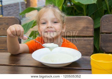 Cheerful Little Girl Eats Porridge For Breakfast