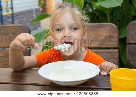 Funny Five-year Girl With Pleasure Eats Porridge For Breakfast