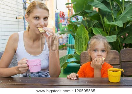 Mom And Daughter Having Breakfast With Tea And Sandwiches Sitting On The Veranda