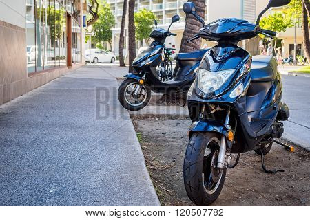 Two black motobikes parked on footpath
