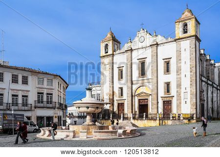 Evora, Portugal - December 1, 2015: Santo Antao Church and the 15th century Henriquina Fountain in the Giraldo Square. Renaissance architecture. UNESCO World Heritage Site.