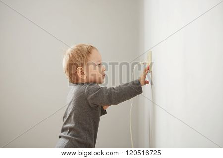 Curious Little Boy Playing With Electric Plug. Trying To Insert It Into The Electric Socket. Danger