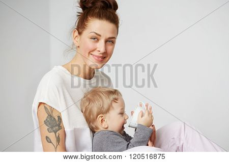 Young Mother With Her One Years Old Little Son Dressed In Pajamas  Gives To Drink Water From Cup In