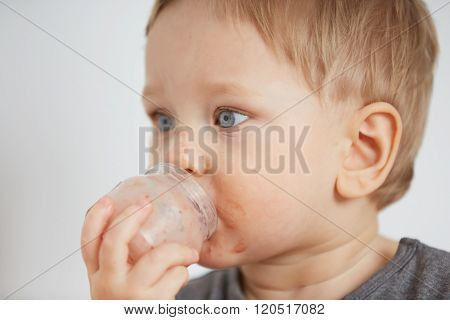 Cute Little Boy Eating Yogurt. Boy Eating A Fruit Smoothie Himself In The Bedroom At The Weekend , L