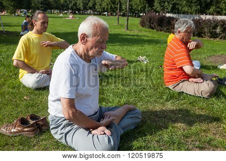 People Meditating In A City Park