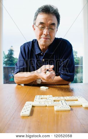 Senior man playing dominos