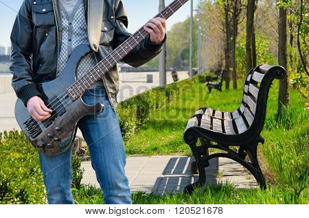A Man Playing The Electric Guitar In The Park