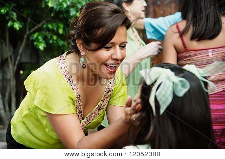 Woman pinching young girl's cheeks