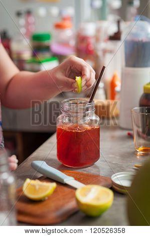 The process of making Thai lemon tea. Woman left hand squeeze lemon into cold tea