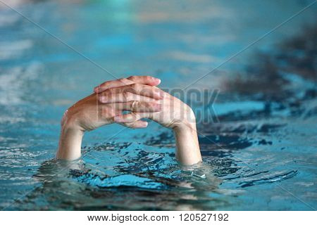two folded hands above water  - body language