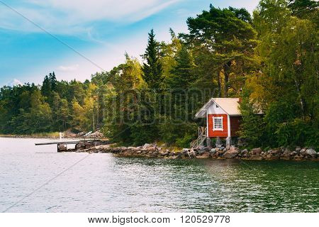 Red Small Finnish Wooden Sauna Log Cabin On Island In Autumn Sea