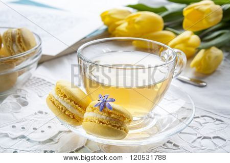 A cup of hot tea, yellow daffodils, sketchbook and lemon macaroons on a light background