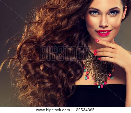 Beautiful model brunette with long curled hair and jewelry necklace