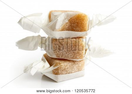 Stack Of Three Wrapped Vanilla Caramel Toffees Isolated.