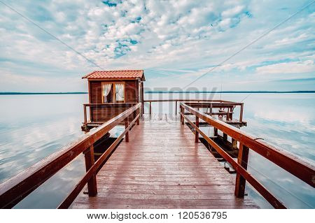 Old wooden pier for fishing, small house shed and beautiful lake