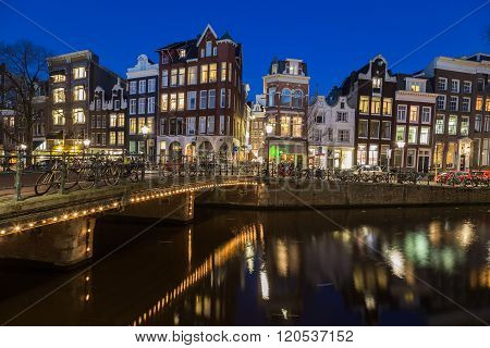 AMSTERDAM NETHERLANDS - 16TH FEBRUARY 2016: A view along the Keizersgracht canal in Amsterdam at night. Reflections buildings bikes and cars can be seen.