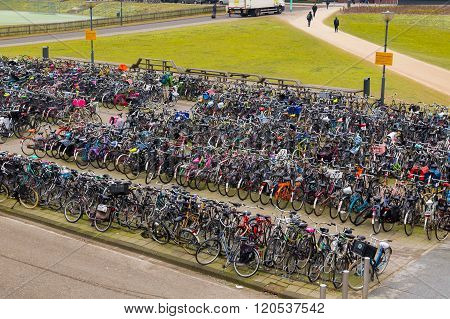 AMSTERDAM NETHERLANDS - 18TH FEBRUARY 2016: Large amounts of bikes parked at a bike rack in Amsterdam. People can be seen.