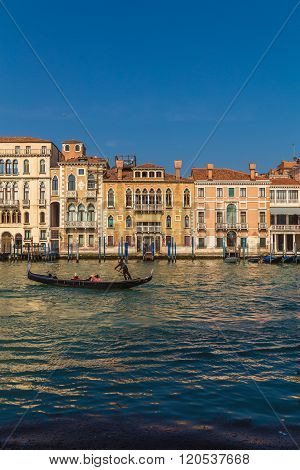 VENICE ITALY - 15TH MARCH 2015: A view of buildings along the Grand Canal in Venice. A Gondola and people can be seen.