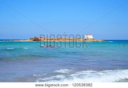 Rocks on the coast of Aegean Sea in Malia Crete Greece. In the background the island Afentis Christos.