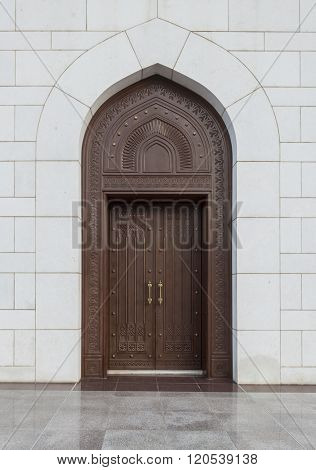 A heavily handcrafted wooden door with intricate Islamic design. Front facade.