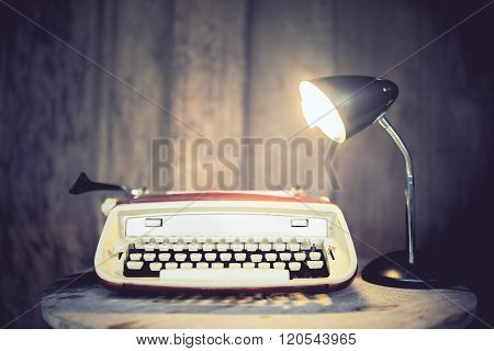Vintage Typewriter With Lamp On Round Wooden Table